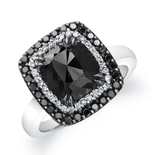 A single rose radiant shaped black diamond weighting 1 1/4 ct, sits surrounded by a halo of 50 sparkling white & black diamonds totaling1/3 ctw. in this unique 14k white gold black diamond ring. This fabulous look is the latest trend worn by many celebrities.